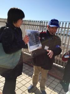 屋上から昔の写真と比較しながら説明してくださるサポーターの黒野さんと岸本さん