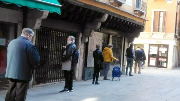 スーパーマーケットの前に距離を保ちつつ並んで入店を待つ人々