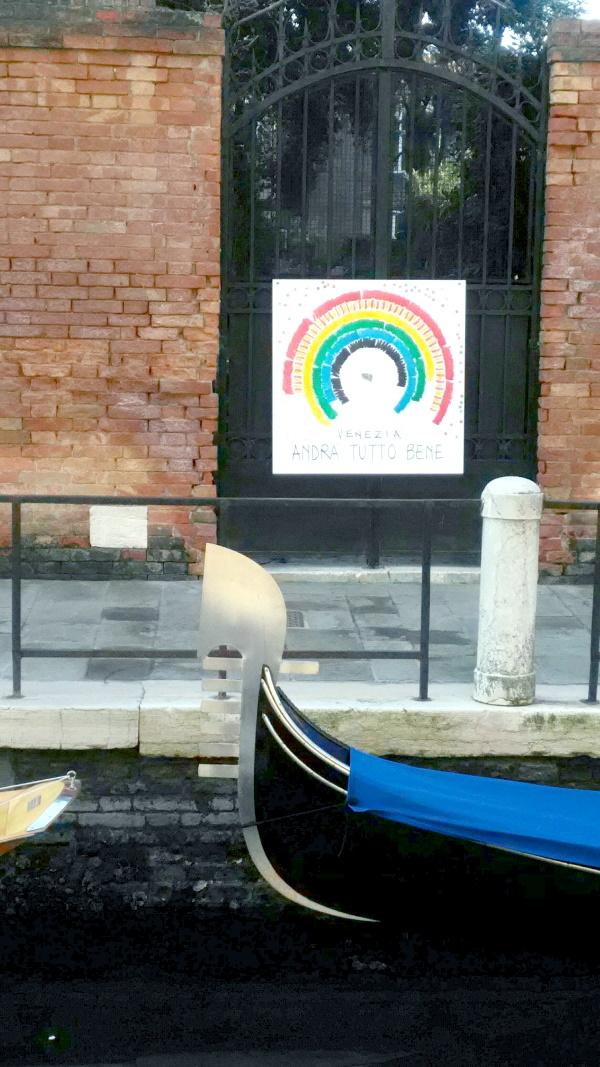 邸宅の門に貼られた「全てうまくいくよ」のメッセージと虹の絵。手前はゴンドラの舳先