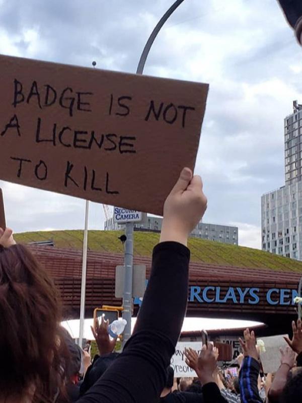 Barclays Center 前でプラカードを持つ女性 Photo:Siarra Maldonado